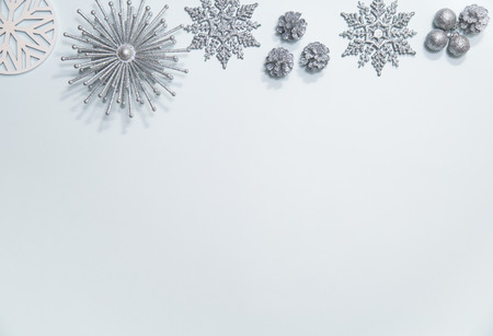 Flat lay of silver glitter snowflakes, stars, ornaments and pinecones arranged in a border on a pale blue background