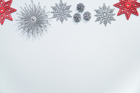 Flat lay of silver glitter snowflakes, stars, ornaments and pinecones arranged in a border with red snowflakes on a pale blue background Stock Photo