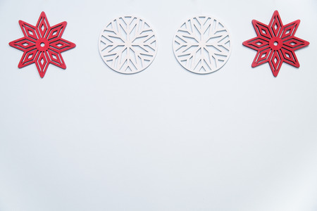 Flat lay of red and white wooden snowflakes arranged in a border on a pale blue background