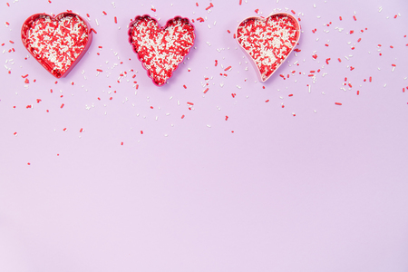 A row of heart shaped cookie cutters filled with red and white sprinkles on a pale purple background