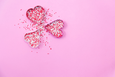 A trio of hearts arranged in a circle with red and white sprinkles on a pink background