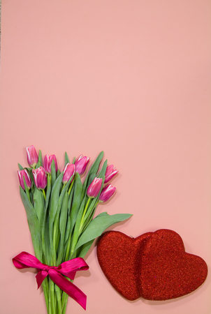 Bouquet of pink tulips with red overlapping glitter hearts on pink Banque d'images - 115500665