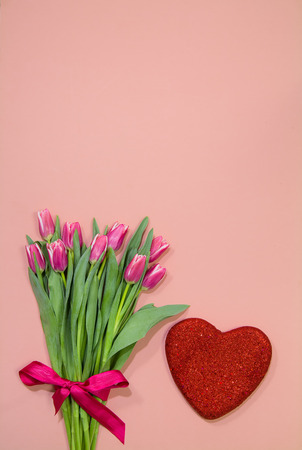 Bouquet of pink tulips with red overlapping hearts on pink Stock Photo