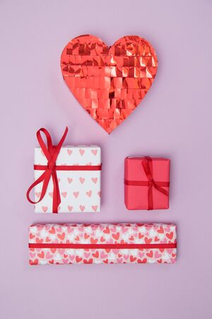 Three wrapped valentines day gifts and a sparkly red heart on a purple background