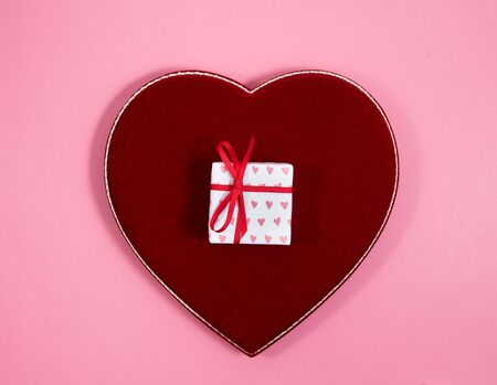 Wrapped Valentine's Day gift and velvet heart shaped box on pink background Banque d'images - 128341064