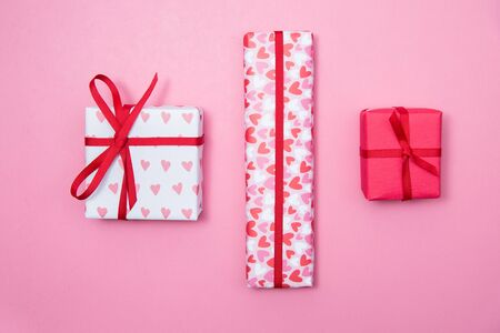 Row of valentines day gifts wrapped in pink and red paper on a pink background Stock Photo