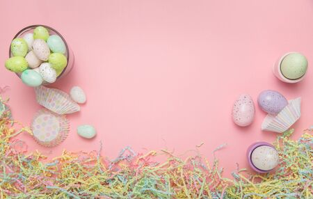 Easter eggs and easter basket filling on a pale pink background Stock Photo