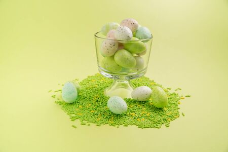 Easter eggs in a clear cup with green and yellow sprinkles on a bright green background Stock Photo
