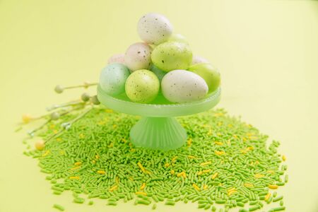 A stack of Easter eggs is piled on a green cake stand with green and yellow sprinkles on a bright green background Stock Photo