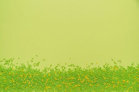 Flat lay of spring green and yellow candy sprinkles along the bottom edge of a bright green background