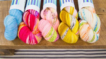 Skeins of vibrant variegated yarn lined up on a rustic wooden table 스톡 콘텐츠