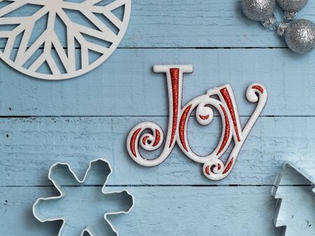 Word Joy on blue plank board background with cookie cutters, christmas ornaments, and snowflake shapes Banque d'images