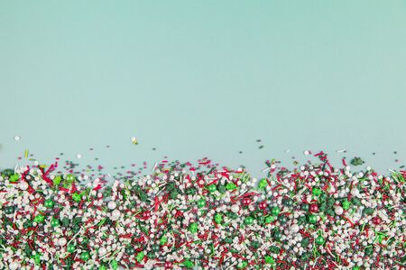 Flat lay of colorful christmas themed sprinkles along the bottom edge of a pastel green background Banque d'images - 137410784