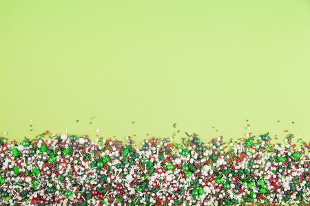 Flat lay of colorful christmas themed sprinkles along the bottom edge of a lime green background