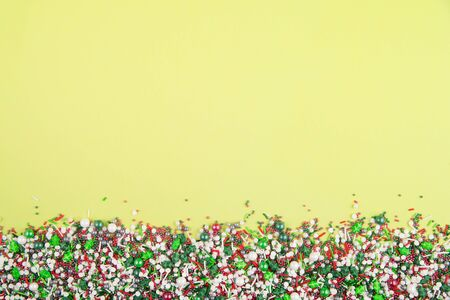 Flat lay of colorful christmas themed sprinkles along the bottom edge of a yellow background