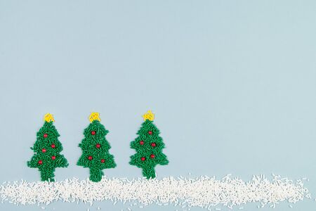 Flat lay of decorated Christmas trees in the snow made out of sprinkles candy on blue background