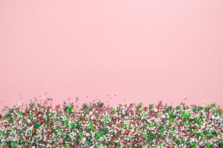 Flat lay of colorful christmas themed sprinkles along the bottom edge of a pink background Banque d'images - 137410789