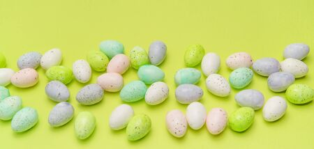 Border of scattered pastel easter eggs on bright green