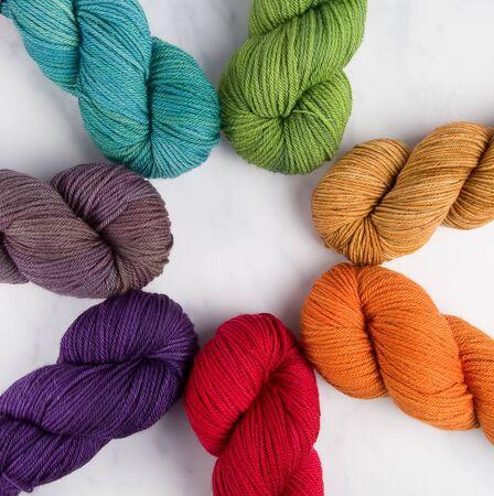A rainbow of woolen yarn hanks arranged in a circle