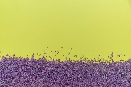 Flat lay of springtime purple candy sprinkles along the bottom edge of a bright green background