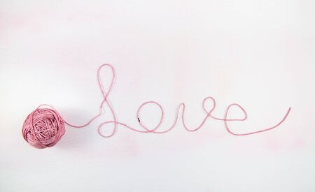 Ball of yarn partially unwound to spell Love on a pale pink