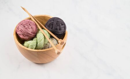 Knitting bowl full of balls of colorful yarn with wooden knitting needles on neutral background