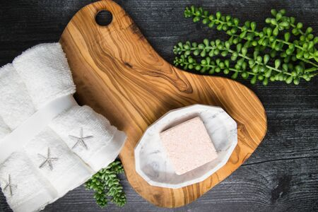 Flat lay of pink foaming bath bomb cube on wooden tray with towels and succulents