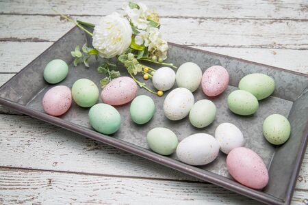 Pastel easter eggs and flowers on a vintage metal tray on a textured wood table Banque d'images