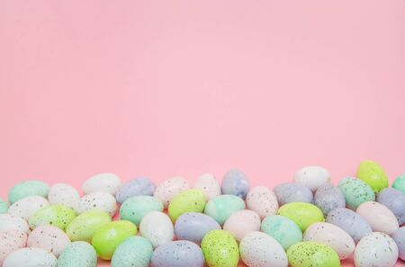 Border of pastel speckled easter eggs on a pink