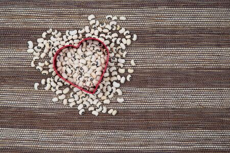 Scattered black eyed peas with heart shape on striped woven placemat