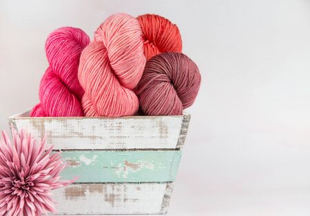 Four skeins of yarn in shades of pink in a white rustic basket