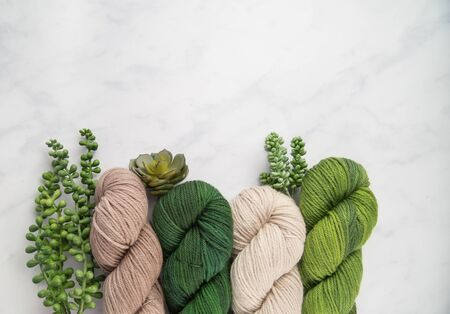 Shades of green and beige yarn with succulents on a marble grey