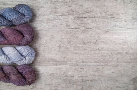 Purple skeins of yarn on a rustic grey wooden table