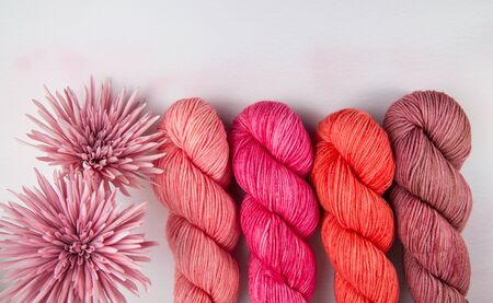 Four hanks of yarn in shades of pink with pale pink flowers