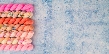A border of pink yarns on a blue speckled background Banque d'images