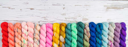 A rainbow border of yarn on a weathered white wood tabletop Banque d'images