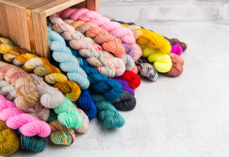 Colorful twists of yarn are stacked on a table