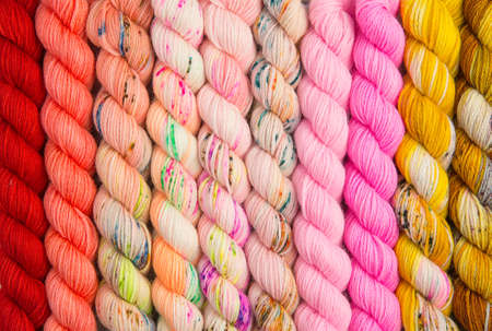 Warm colored hues of yarn twisted into hanks