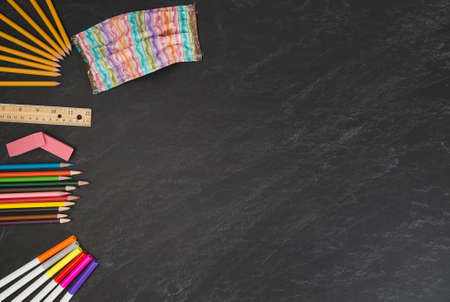 Brightly colored striped face mask with back to school supplies on chalkboard