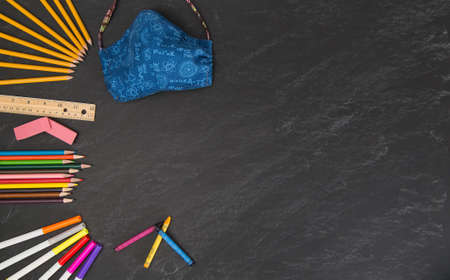 Science theme face mask with back to school supplies on a grey chalkboard