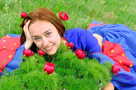 gipsy: gipsy girl in blue, lying on green grass with a flower