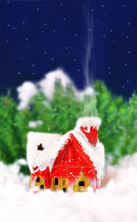 Christmas card with a house in the woods and snowing photo