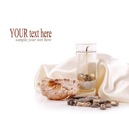 burning candle with sea shells and sea stones on a white background photo