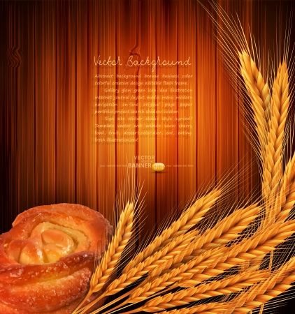 golden ears of wheat and bread roll on a wooden background