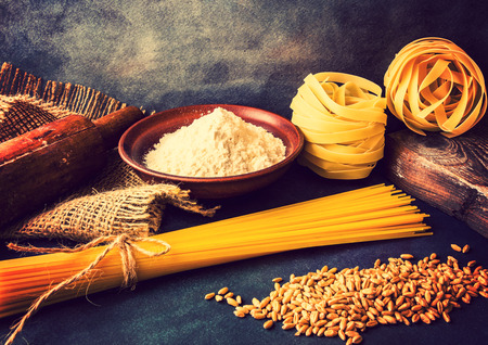 Italian pasta, spaghetti, fettuccine, wheat, rolling pin, flour on a textured background. Still life in a rustic style.  Vintage version Stock Photo