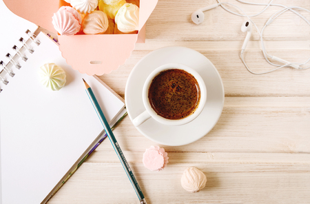 Morning coffee with a notebook and a pencil, with a box filled with small meringues, headphones on a wooden light background.Топ view.