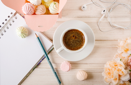 morning coffee with a notebook and a pencil, with a box filled with small meringues, headphones on a wooden light background.