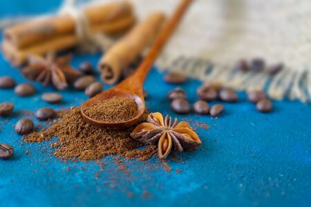 coffee grains scattered on a blue textural background, anise stars, cinnamon sticks and ground coffee in a wooden spoon.