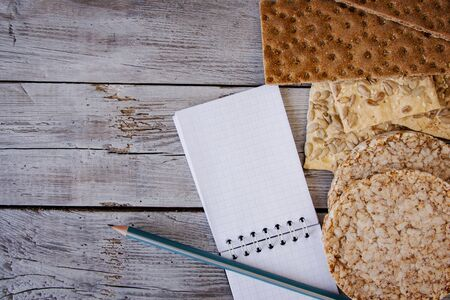 useful dietary, crispbread, flakes, buckwheat, cookies with sunflower on a textured background. A sheet of pencil paper to write your text. Zdjęcie Seryjne