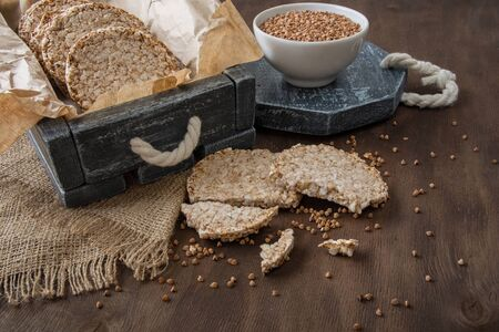 Round dietary loaves of airy buckwheat  in vintage box and a cup of raw buckwheat on wooden background Zdjęcie Seryjne